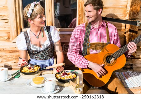 Couple on mountain hut eating Kaiserschmarrn, a traditional Austrian pancake - stock photo