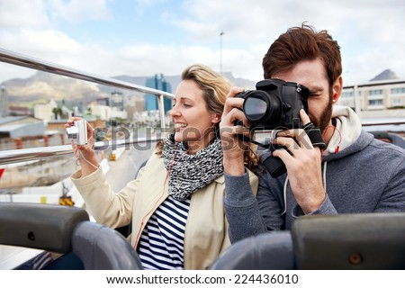 couple on open top tourist bus in city taking photos on vacation - stock photo