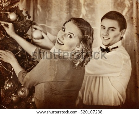 Couple on party decoration Christmas tree. Black and white retro.Old photo on yellow paper.