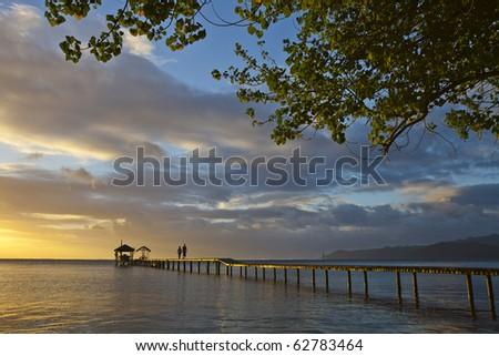 Couple on pontoon at sunset - stock photo