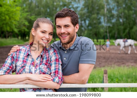 Couple on ranch. Happy young loving couple standing close to each other and smiling while standing on ranch with horse walking in the background - stock photo
