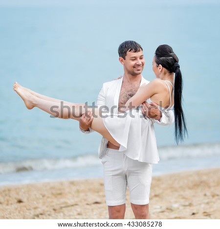 Couple on seashore in cloudy day. Young man holding his girlfriend - stock photo