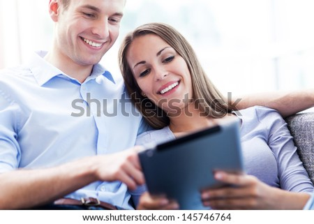 Couple on sofa with digital tablet  - stock photo