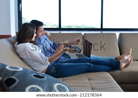 Couple on sofa with TV remote - stock photo