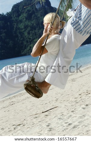 Couple on swing at beach - stock photo