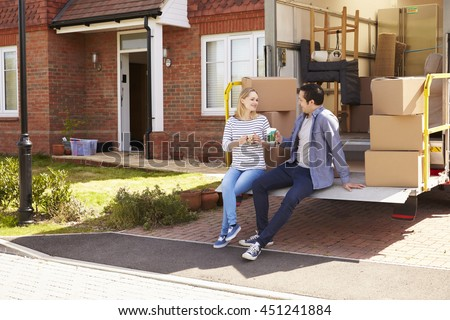 Couple On Tail Lift Of Removal Truck Moving Home - stock photo