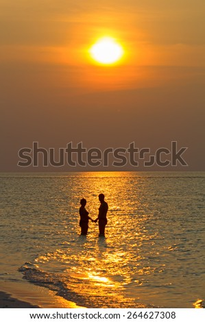 Couple on the beach at sunset - stock photo