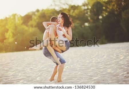 Couple on the beach having fun, going crazy - stock photo
