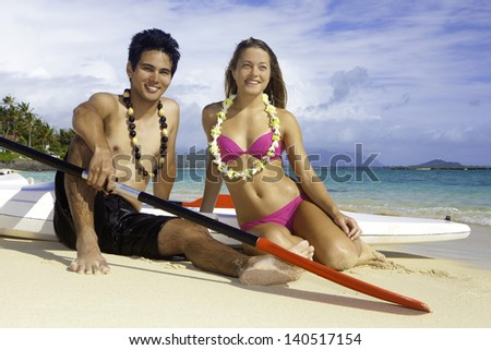 couple on the beach with their paddle boards - stock photo