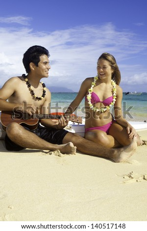 couple on the beach with their surf skis playing ukulele - stock photo