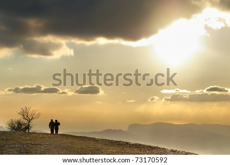 Couple on the hill against sunset. Landscape with clouds and sky.