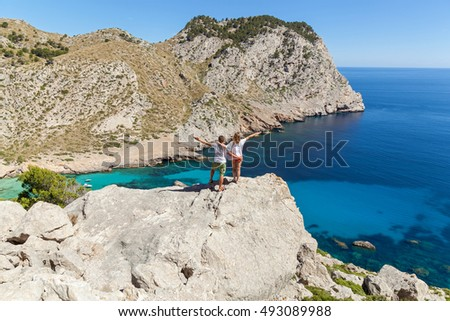 Couple on the mountain. Lovely happy couple posing from the back on the rocky coast of Mallorca.