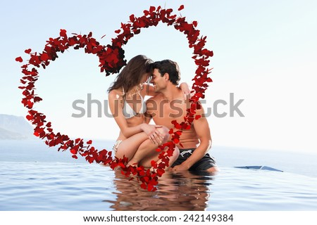 Couple on the pool edge against heart made of petals - stock photo
