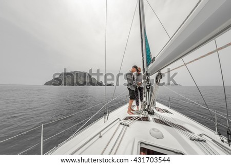 Couple on the sailing boat in a sea with island on the horizon