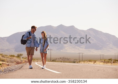 Couple On Vacation Hitchhiking Along Road - stock photo