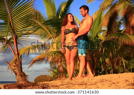 couple on vacations , young couple in love on holidays Vacation couple walking on beach together in love holding around each other. Happy interracial young couple valentine day - stock photo