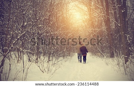 Couple on winter path in forest on a sunny day - stock photo