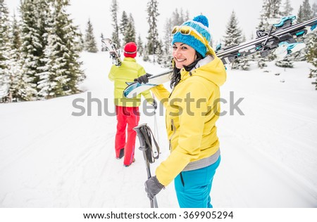 Couple on winter vacation - Portrait of pretty woman carrying ski and smiling at camera - stock photo