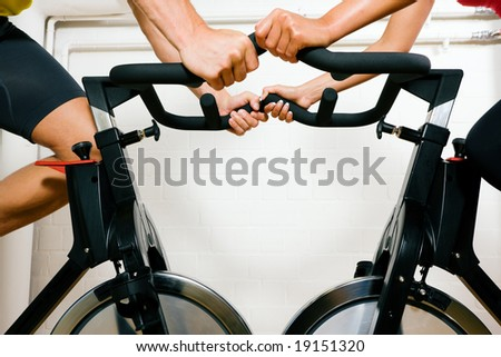 Couple (only limbs to be seen) training on bicycles in the gym