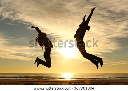 Couple or friends silhouette jumping on the beach at sunset with a warmth light and the sun in the middle - stock photo