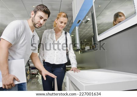 Couple or owner showing client in furniture store looking faucets and sinks for removals and home decorating - stock photo
