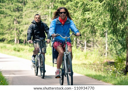 Couple outdoors on bike. Bicycle path from St. Candid in italy to Lienz in austria. - stock photo