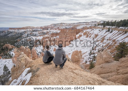 Couple overlooking trail in Bryce Canyon National Park, a sprawling reserve in southern Utah, is known for crimson-colored hoodoos, which are spire-shaped rock formations.