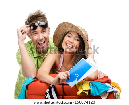 Couple packs up suitcase with clothing for departure, isolated on white. Concept of romantic vacations and lovely honeymoon - stock photo