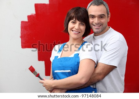 couple painting a wall in red - stock photo