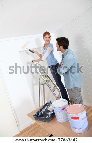 Couple painting new apartment - stock photo