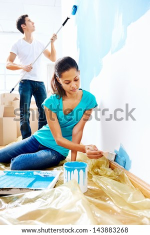 couple painting new home together with blue color happy and carefree relationship - stock photo