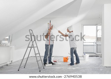Couple painting the new apartment - stock photo