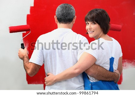 Couple painting wall in red - stock photo