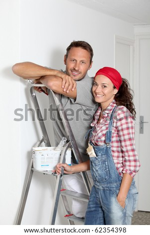 Couple painting walls of their new home