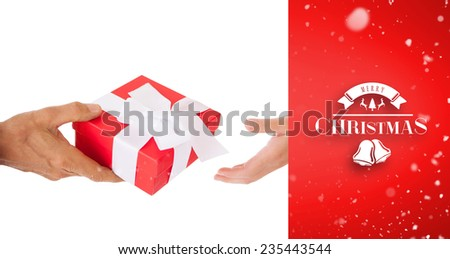 Couple passing a wrapped gift against red vignette - stock photo