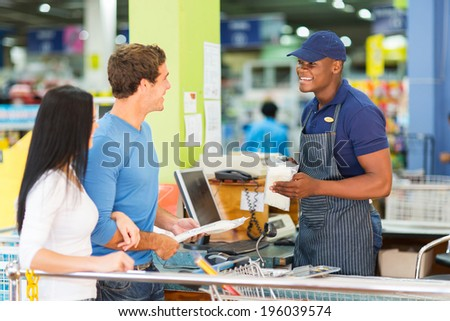 couple paying at hardware store till point  - stock photo