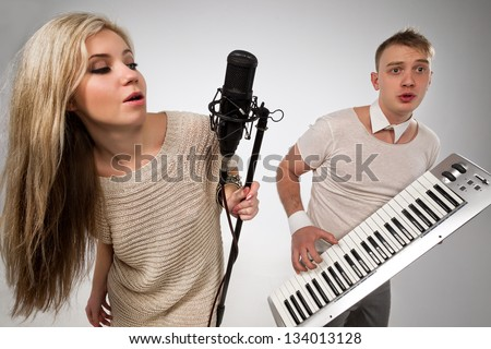 Couple performs duet singing microphone and playing on synthesizer - stock photo