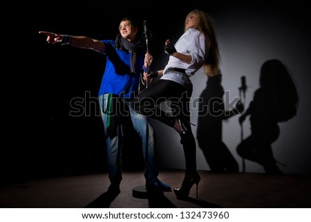 Couple performs duet singing same microphone to everybody. - stock photo