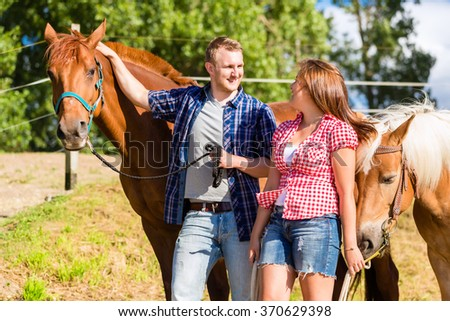 Couple petting horse on pony stable - stock photo