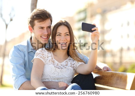 Couple photographing a selfie with a smart phone in a park with an urban background in a sunny day