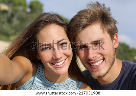 Couple photographing a selfie with the smart phone or digital camera outdoors in the mountain