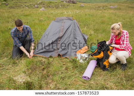 Couple pitching their tent in the countryside