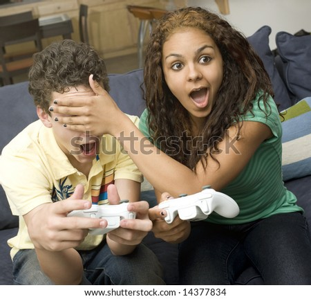 Couple play video games on couch - stock photo