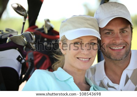Couple playing a round of golf - stock photo