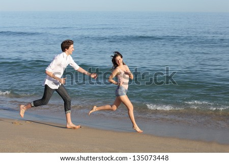 Couple playing and running on the beach shore near the water - stock photo
