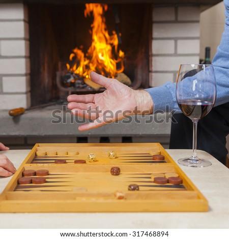 couple playing backgammon at fireplace - stock photo