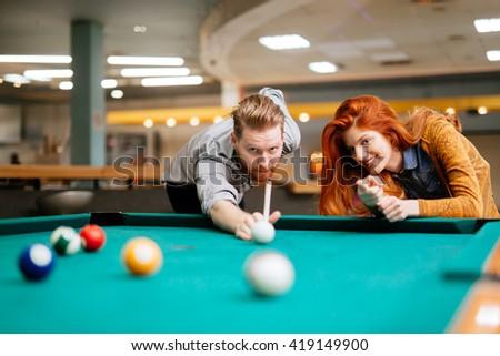 Couple playing billiards and bonding - stock photo