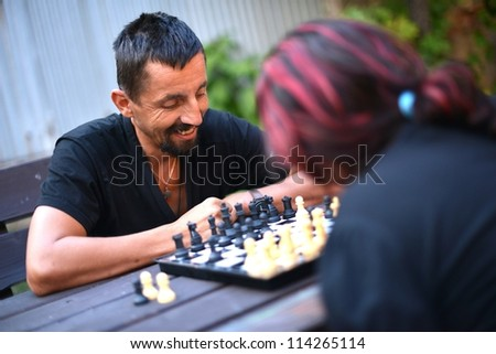 Couple playing chess in the park - stock photo