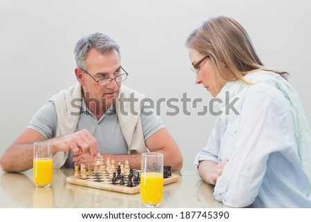 Couple playing chess while having orange juice at home