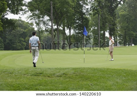 Couple playing golf on golfing course - stock photo